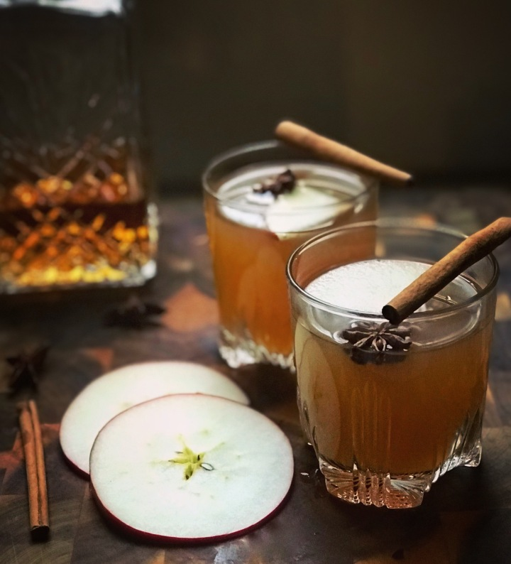 Whiskey and Apple Cider Topped with Fresh Cinnamon Sticks, Star Anise, and Apples